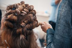 The hairdresser does hair extensions to a young girl. 2018 royalty free stock photography