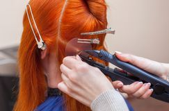 The hairdresser does hair extensions to a young girl in a beauty salon. Professional hair care stock photo