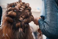 The hairdresser does hair extensions to a young girl. 2018 royalty free stock images
