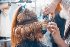 The hairdresser does hair extensions to a young girl. 2018 royalty free stock photos