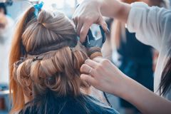 The hairdresser does hair extensions to a young girl. 2018 royalty free stock image
