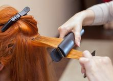The hairdresser does hair extensions to a young girl, a redhead girl in a beauty salon. Professional hair care royalty free stock image