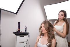 Hairdresser does hair style of woman in Stock Images