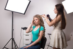 Hairdresser does hair style of woman in Royalty Free Stock Images