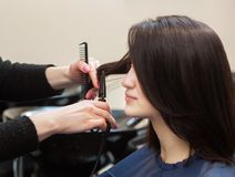 The hairdresser does a haircut with hot scissors of hair to a young girl. A brunette in a beauty salon Stock Images