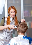 The hairdresser does a  hairstyle to the client Stock Photos