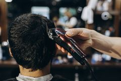 Hairdresser doing hair in the barber shop with clipper.  stock photos