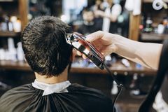 Hairdresser doing hair in the barber shop with clipper.  stock image