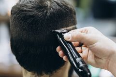 Hairdresser doing hair in the barber shop with clipper.  stock images