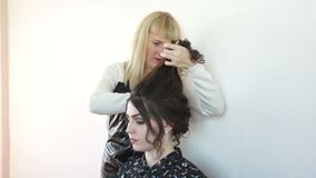 Hairdresser doing hair girl. Hairdresser makes hairstyle on the girl with the dark hair stock video footage