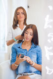 Hairdresser doing haircut for women wiht mobile phone in hairdre Stock Photography