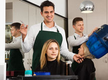 Hairdresser doing hairstyle of blonde females at salon Royalty Free Stock Photography