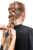 Hairdresser doing up one's hair in a plait Stock Images