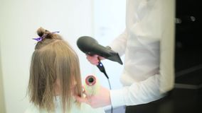 Hairdresser dries the girl's hair with dryer.  stock video footage