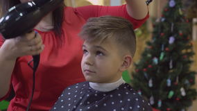 Hairdresser dries hair baby. Barber blowing drying hair little happy boy. Smiling kid in barbershop. Men`s hairstyling using hairdryer and comb stock video