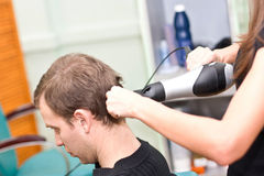 Hairdresser dries the hair client in a beauty sal Royalty Free Stock Photo