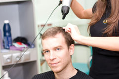 Hairdresser dries  hair guy Stock Photos