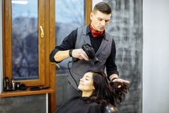 Hairdresser dries hair with a hairdryer in beauty salon stock images