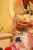 Hairdresser dries the hair of a little blonde girl in a beauty salon Royalty Free Stock Photo