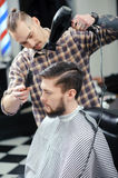 Hairdresser dries hair of a male client royalty free stock images