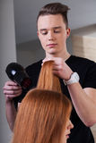 Hairdresser is drying customer hair Royalty Free Stock Photo