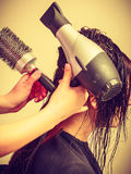 Hairdresser drying dark female hair using professional hairdryer Stock Images