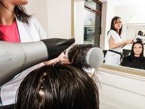 Hairdresser drying dark female hair using professional hairdryer Stock Photos