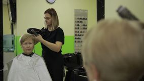 Hairdresser drying female customer`s hair in salon stock video