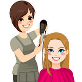 Hairdresser Drying Hair. Beautiful hairdresser working drying and combing hair of customer woman Royalty Free Stock Photos