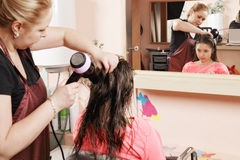 Hairdresser drying teenager hairs Stock Photo