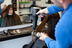 Hairdresser drying woman's hair Royalty Free Stock Photo
