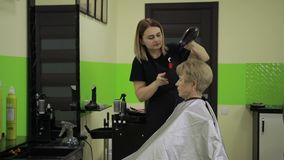 Hairdresser drying woman`s hair using hair dryer stock video