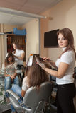 Hairdresser dye  hair. Hairdresser dye his hair long-haired girl Royalty Free Stock Photography