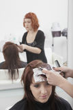 Hairdresser Dyeing A Young Woman's Hair Stock Photo