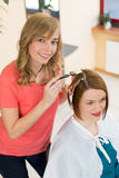 Hairdresser dying hair of client Stock Photography