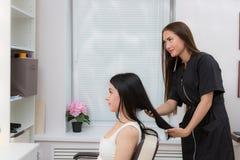 Hairdresser examines client`s hair