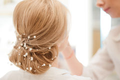 Hairdresser finishing bride`s hairstyle Royalty Free Stock Images