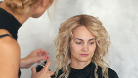 Hairdresser fixes lacquer curls in beauty salon. Close up stock footage