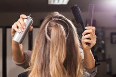 Hairdresser fixing hairdo of a model with a hair spray royalty free stock images