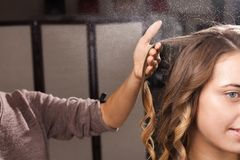 Hairdresser fixing ringlets of a girl with a hair spray royalty free stock photography