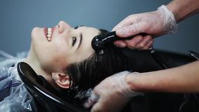 Hairdresser in gloves washing brunette girl hair over sink in beauty shop. stock video