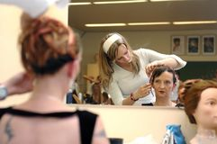 Hairdresser, hair dressing 3. A daughter working on mother's hair at a school exam Stock Image