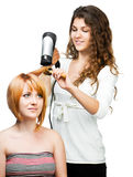 Hairdresser with hair dryer. Professional hairdresser with hair dryer at salon with female customer stock photo