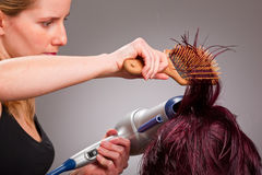 Hairdresser with hair dryer. Hairdresser at work with hair dryer and hairbrush stock image