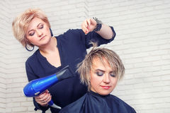Hairdresser with hair dryer Stock Images