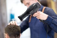 Hairdresser with hair dryer drying male head. Grooming, hairdressing and people concept - male hairdresser or barber with hair dryer drying client`s head at stock photos