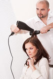 Hairdresser with hair dryer at salon with customer Stock Image