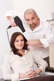 Hairdresser with hair dryer at salon with customer Stock Photo