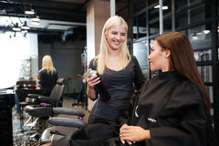 Hairdresser with hair spray fixating client hairdo at salon Royalty Free Stock Images