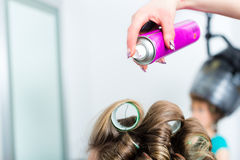 Hairdresser - hair stylist curling hairs. A female customer gets a haircut royalty free stock photo